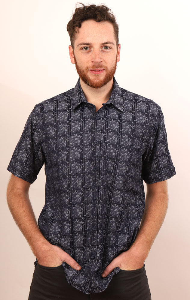 MAN SMILES WITH HANDS IN FRONT POCKETS WEARING SHORT SLEEVE WOVEN SHIRT IN NAVY