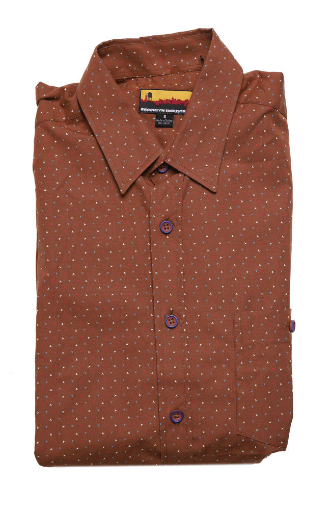 folded Men's long sleeved woven shirt, in a rusty brown tone, featuring blue white and red small graphic markings across the whole body