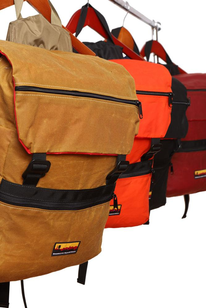 group shot of Mass Backpacks hanging from hangers. Whiskey, Orange, Black and Burgundy
