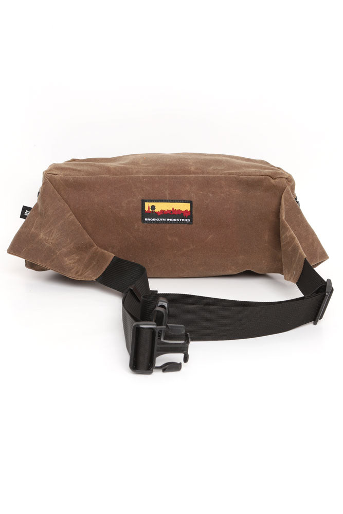 THE ZEKI WAISTPACK IN HAVANNA BROWN WAX CANVAS, BACK VIEW SHOWING SKYLINE LOGO