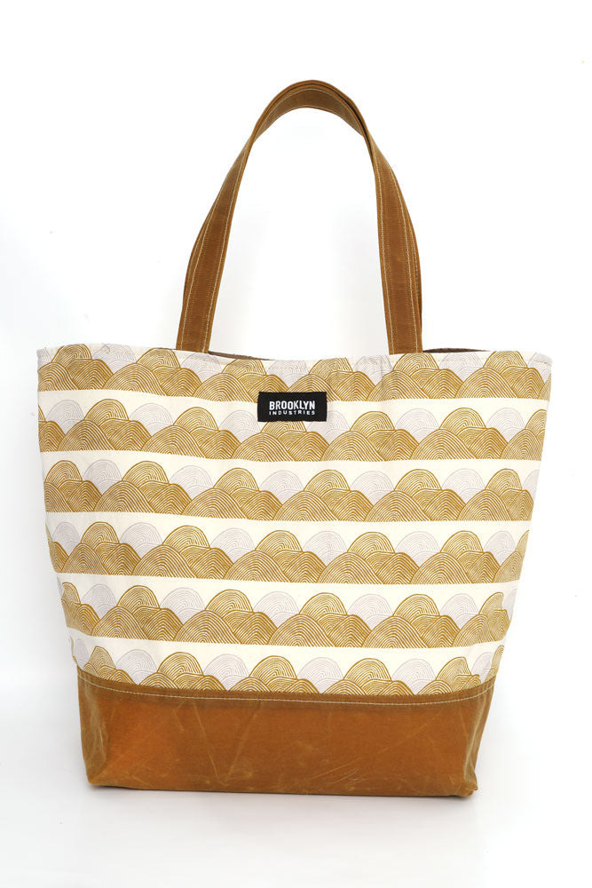 Large cotton canvas tote with waxed canvas handles and bottom.  silver and gold organic wave like pattern pattern with toast wax details, front view