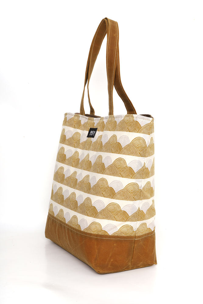 Large cotton canvas tote with waxed canvas handles and bottom.  silver and gold organic wave like pattern pattern with toast wax details, side view