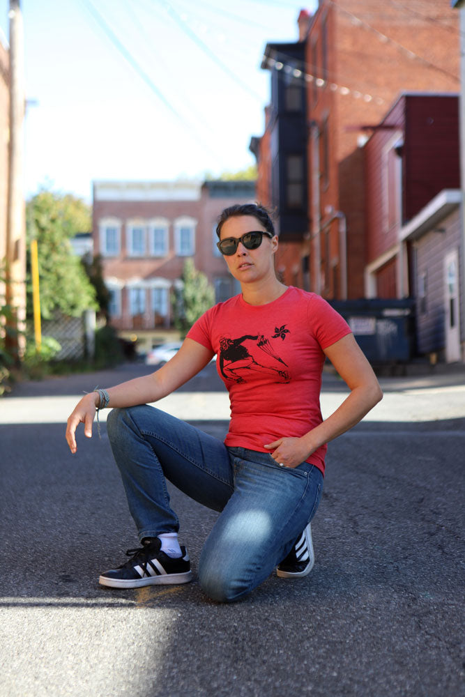 WOMEN CROUCHES IN THE STREET WITH SUNGLASSES ON IN PROTEST T-SHIRT