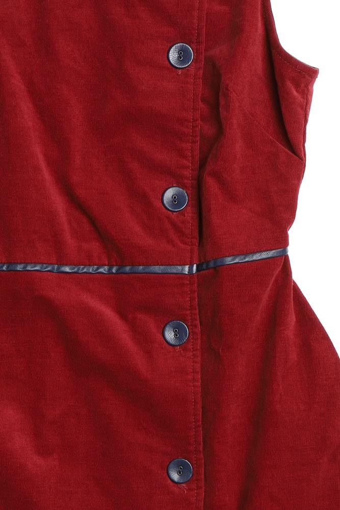 detail of flat lay ruby corduroy dress with button details