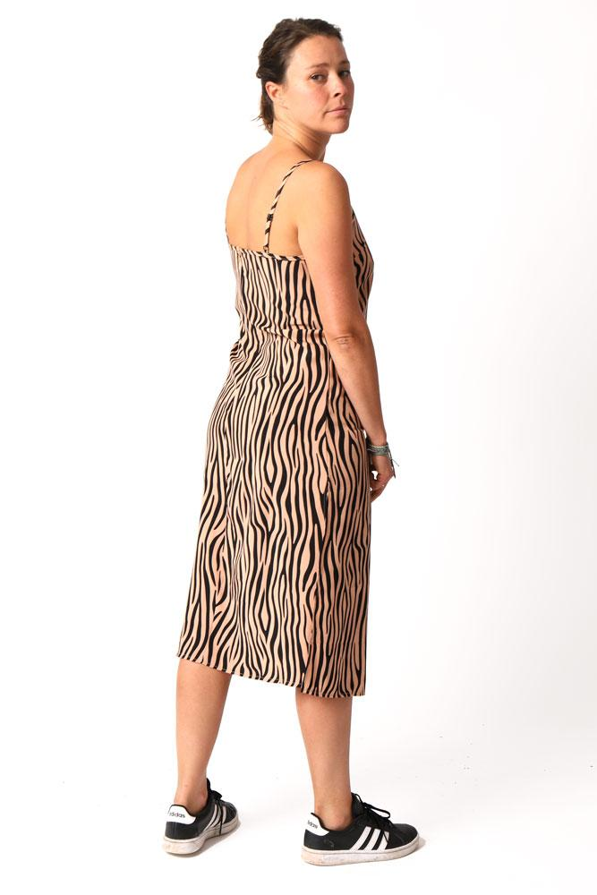 women stands with back to you, looking over shoulder, showing off the back of the leopard print slip dress that hits mid shin