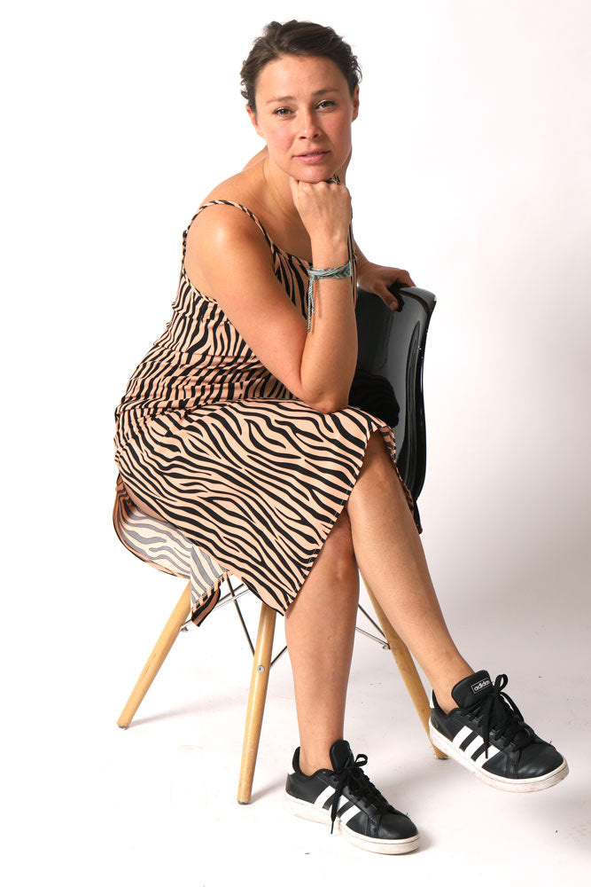 women sits cross legged in chair, showing slit in side of the leopard print slip dress, chin resting on her balled fist.
