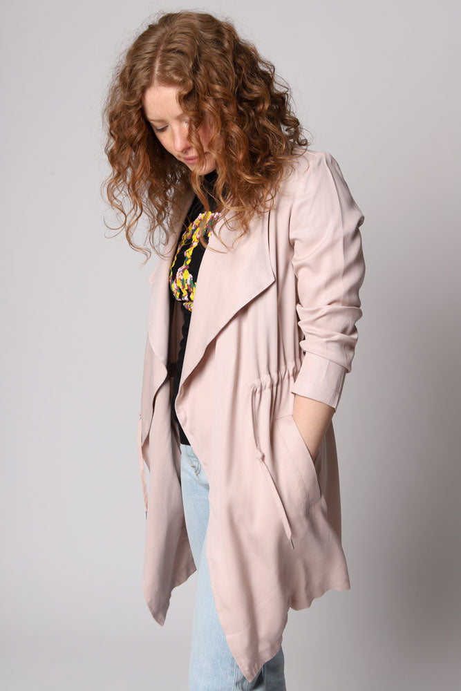 The Let It Rain is an ultra soft Lyocell trench coat with an open front and a cinchable drawstring waist and tie details. Pockets at the hip.