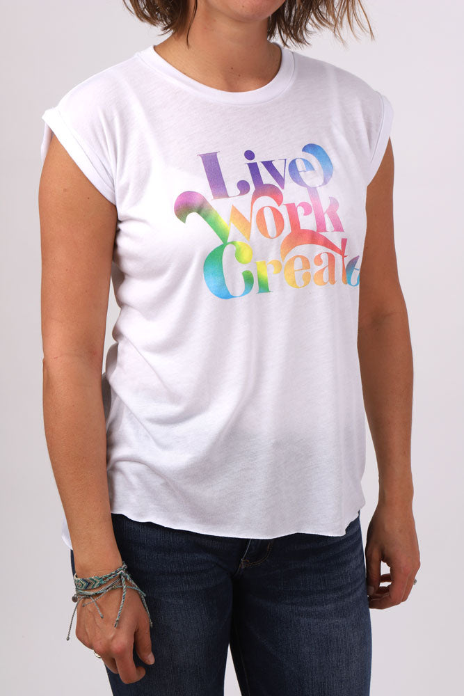women wears jeans and sheer capped sleeve white shirt with live work create in rainbow retro text