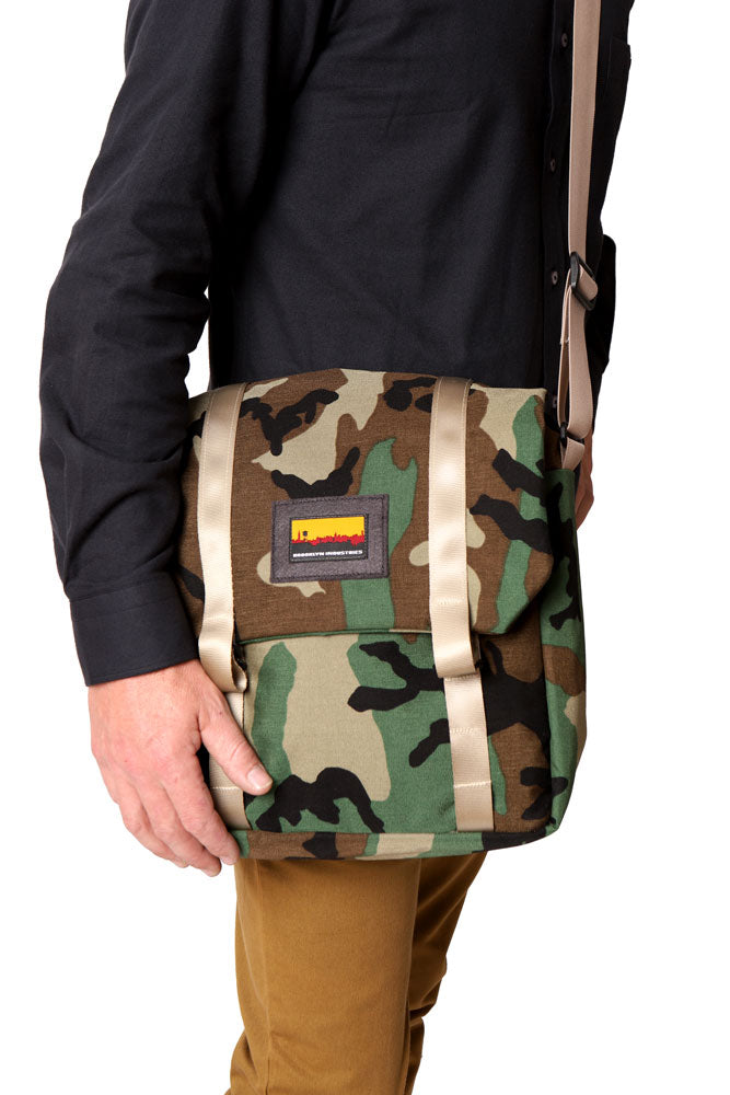 man in black shirt and brown pants, carries a woodland camo messenger style bag with khaki webbing detail over his body on the right side. resting his hand on the bag.  made in the Hudson Valley of New York.