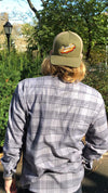 Man wearing olive bk platform script cap stands with back to you, in Prospect Park Brooklyn NY in grey flannel plaid long sleeve dress shirt