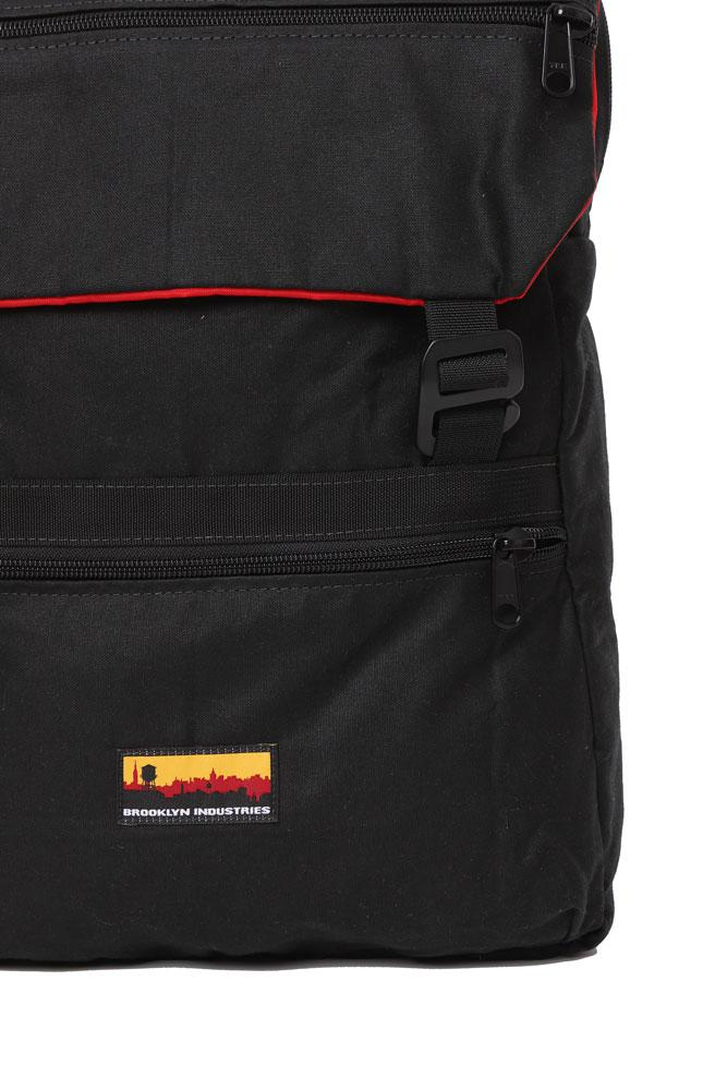 detail view Mass Backpack, with Brooklyn industries logo tag on front pocket, flip over top with contrasting lining, in black waxed canvas