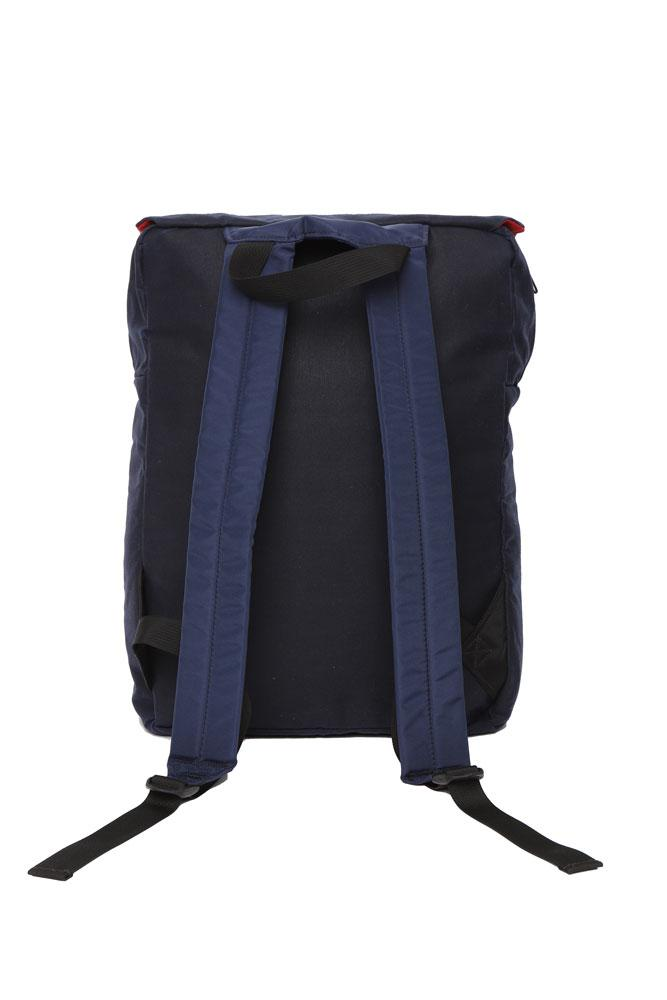 back view of Mass Backpack, with Brooklyn industries logo tag on front pocket, flip over top with contrasting lining, in navy waxed canvas