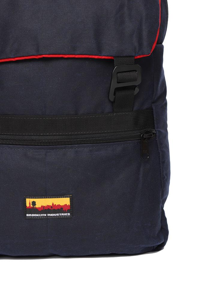 detail view of Mass Backpack, with Brooklyn industries logo tag on front pocket, flip over top with contrasting lining, in navy waxed canvas