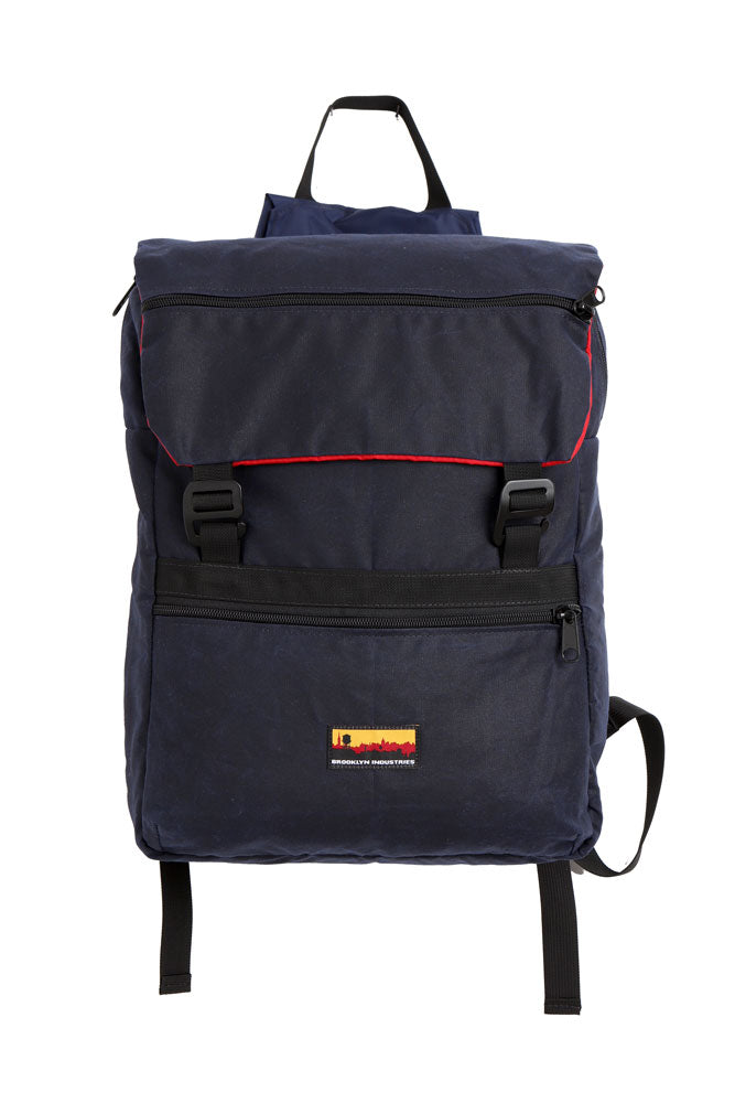flat lay Mass Backpack, with Brooklyn industries logo tag on front pocket, flip over top with contrasting lining, in navy waxed canvas