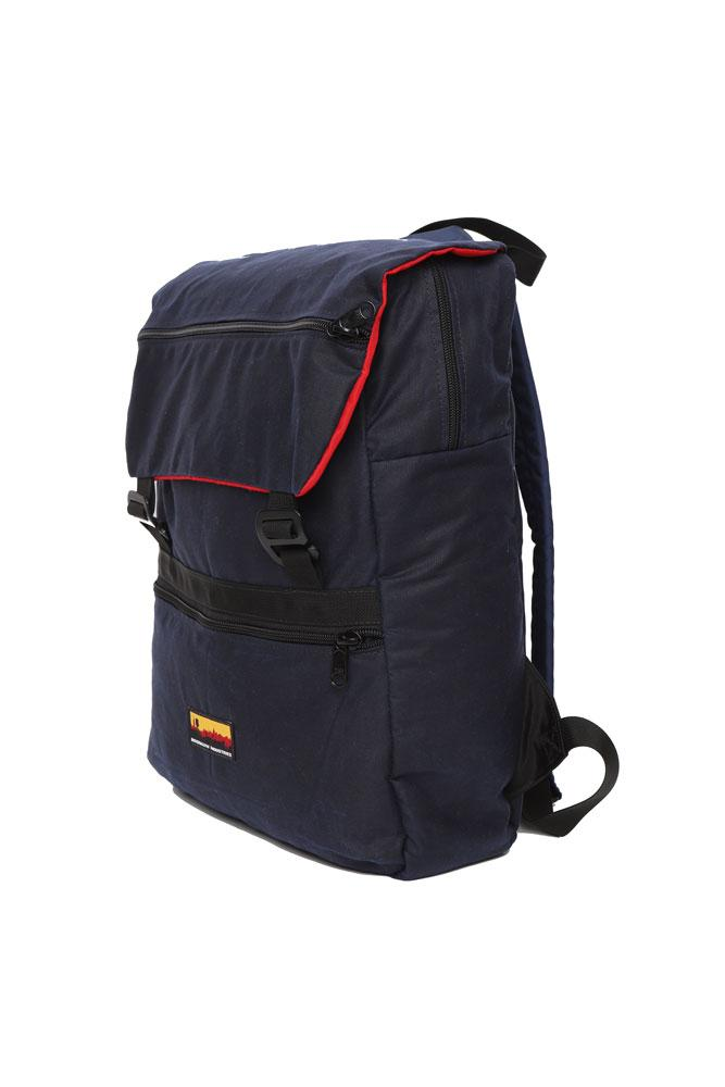 side view Mass Backpack, with Brooklyn industries logo tag on front pocket, flip over top with contrasting lining, in navy waxed canvas