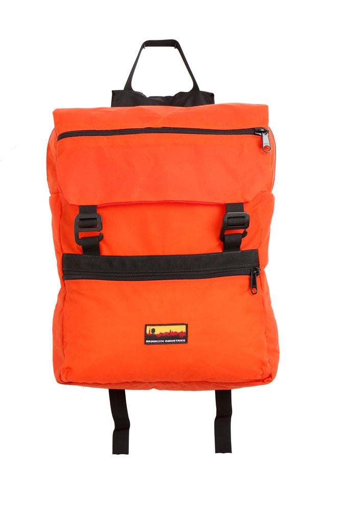 flat lay Mass Backpack, with Brooklyn industries logo tag on front pocket, flip over top with contrasting lining, in orange waxed canvas