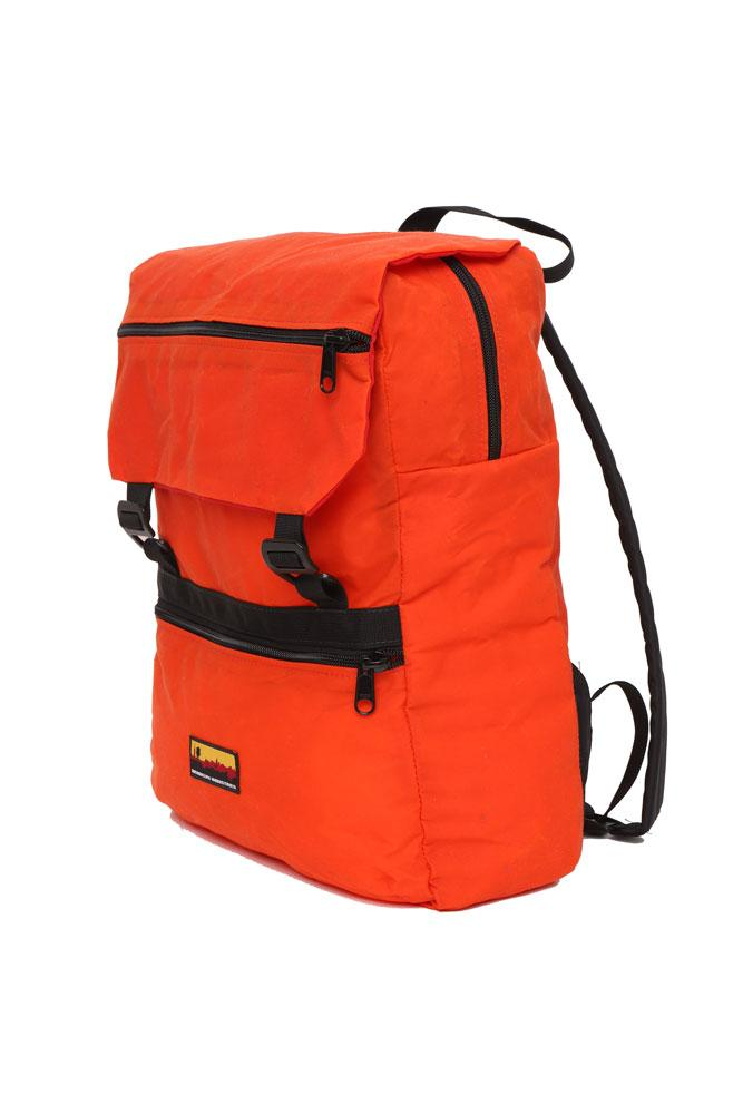 side view of Mass Backpack, with Brooklyn industries logo tag on front pocket, flip over top with contrasting lining, in orange waxed canvas