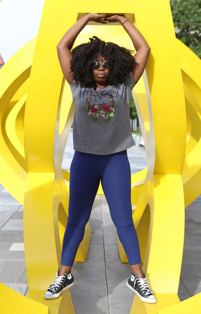 WOMEN BALANCES IN YELLOW ART SCULPTURE WEARING GREY SLUB NATURE SOUNDS T-SHIRT