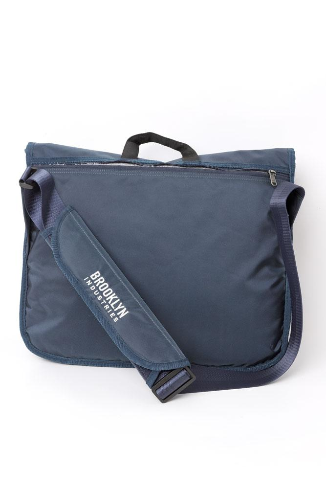 REFLEX MESSENGER BAG IN NAVY SITTING BACK VIEW WITH PADDED BROOKLYN INDUSTRIES EMBROIDERED SHOULDER PAD SHOWING