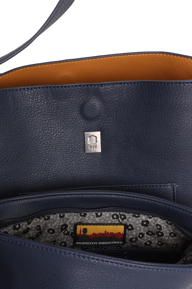 detail of toast lining in navy pebble vegan tote bag, and the patterned lining in the crossbody bag