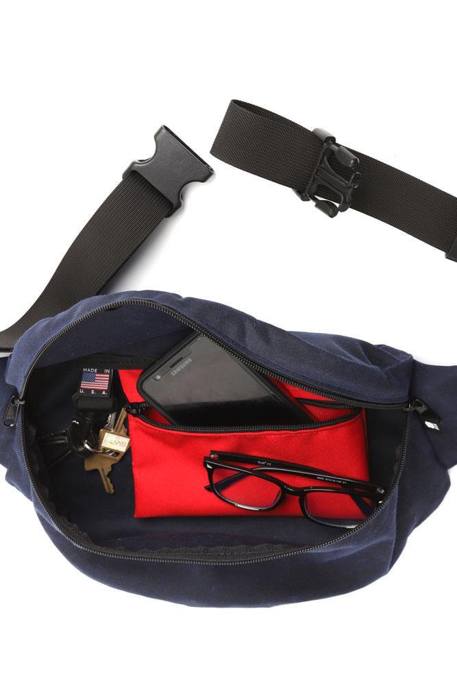 INTERIOR SHOT OF ZEKI WAISTPACK WITH RED ZIPPER POCKET, CLIP FOR KEYS ,MADE IN USA LABEL.