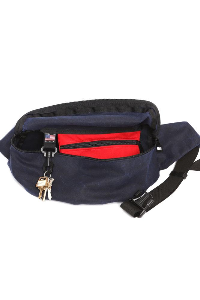 FRONT VIEW OF OPEN OF WAXED CANVAS FANNY PACK - NAVY  SHOWING KEY CLIP AND POCKET INSIDE.