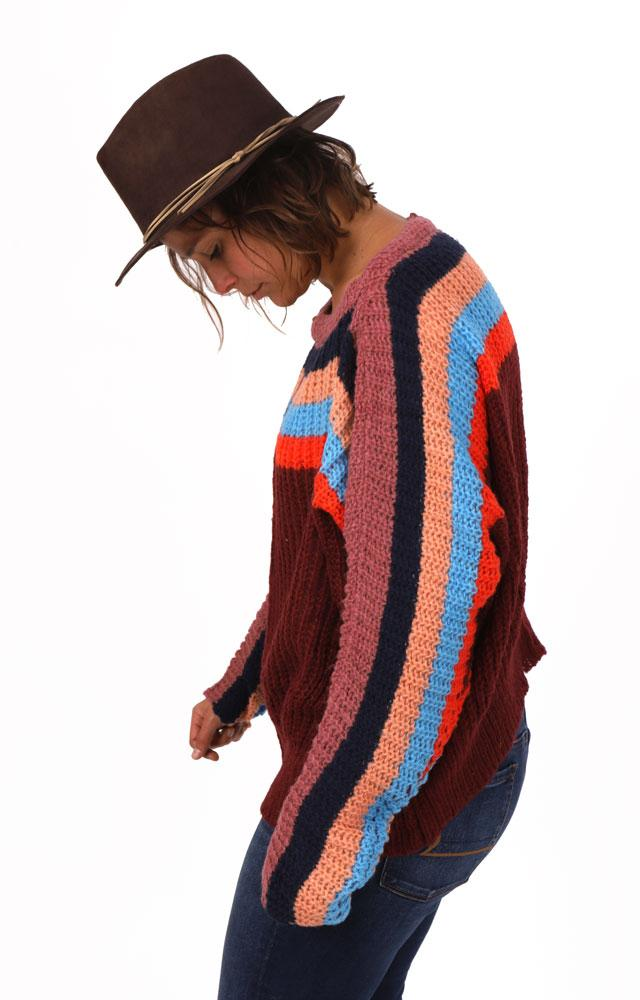 side view of women looking down in brown brimmed hat, wearing a maroon bodied chunky sweater with red, blue orange and light pink stripes