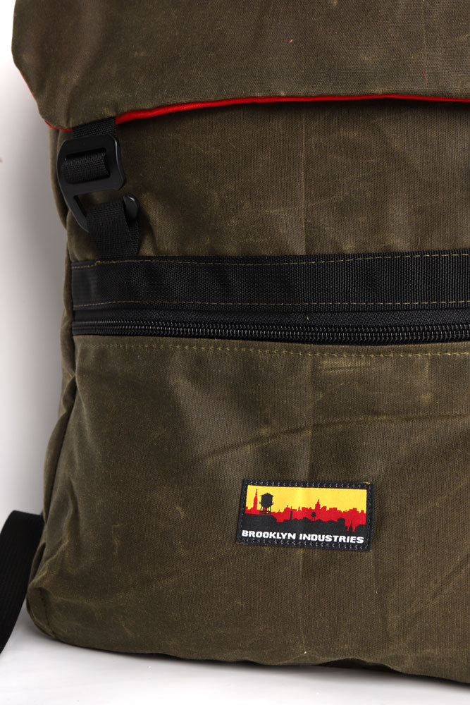 detail of olive green waxed canvas back pack with sky line brooklyn industries patch on the center front pocket