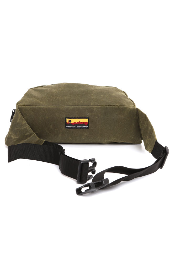 ZEKI WAIST PACK IN OLIVE WAX CANVAS  back view of skyline logo