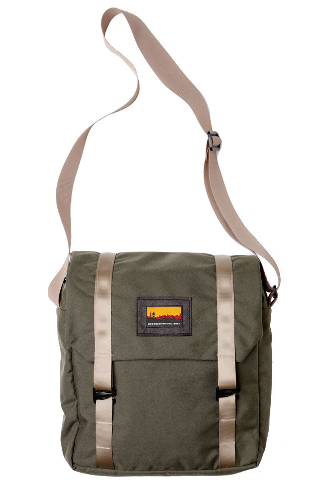 cross body style bag with a flip top and khaki webbing straps. flat lay image of the mail bag in ranger green