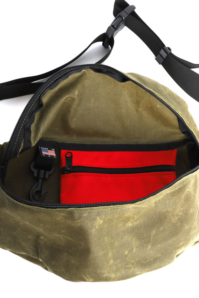 ZEKI WAIST PACK IN OLIVE WAX CANVAS  INTERIOR VIEW SHOWING KEY CLIP AND CORDURA POCKET IN RED
