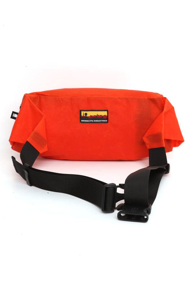 BACK VIEW OF ORANGE WAXED CANVAS FANNY PACK WITH THE SKYLINE LOGO