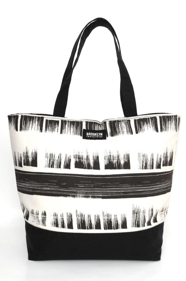 Large cotton canvas tote with waxed canvas handles and bottom.  black and white brushed textured pattern with black wax details, front view