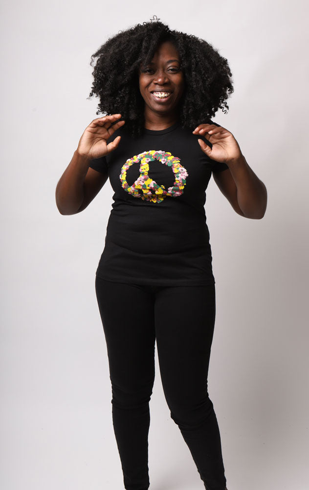 SMILING WOMEN IN BLACK T-SHIRT WITH A PEACE SIGN OF FLOWERS IN BRIGHT COLORS