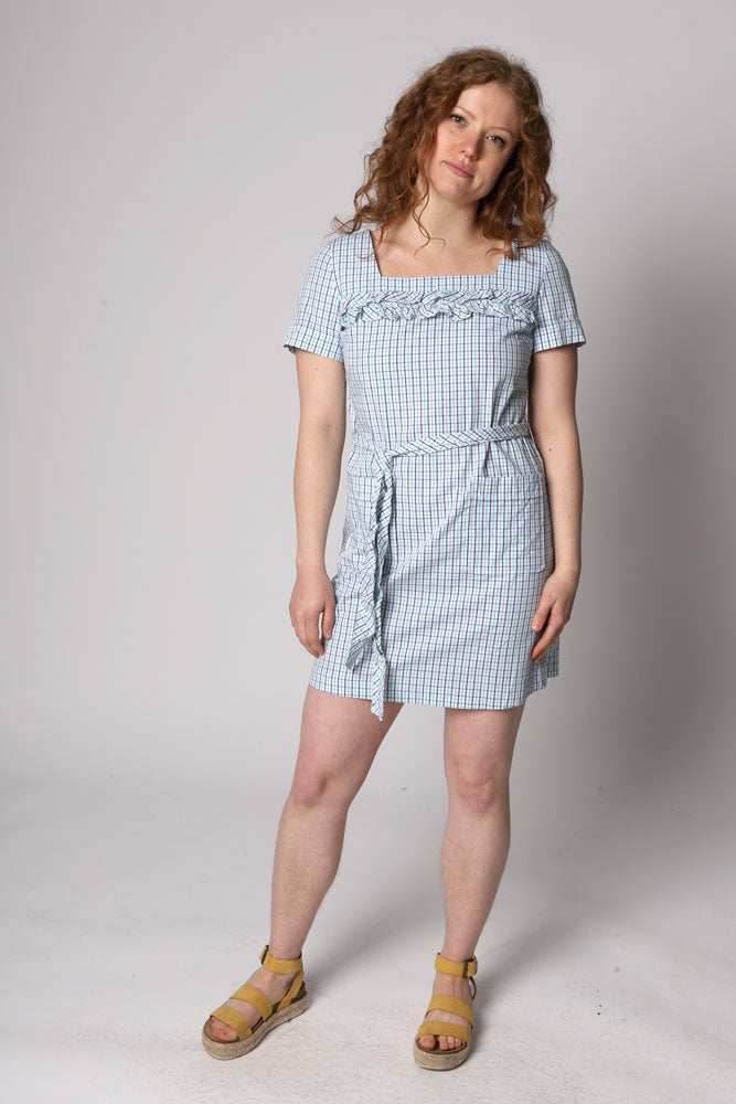plaid dress with a square cut neck, short sleeves and a ruffle across the chest.  A tie waist detail and a zipper up the back. Light weight, cute front pocket detail.