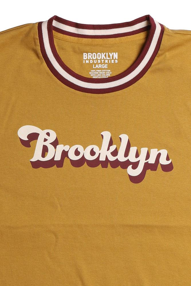 DETAIL OF BROOKLYN SCRIPT ON GOLD SHIRT WITH MAROON AND WHITE RIMMED COLLAR
