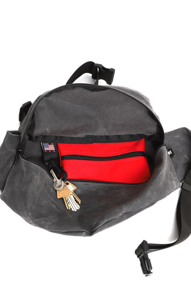 interior view of zeki waist pack in rhino wax with red zipper pocket and key clip