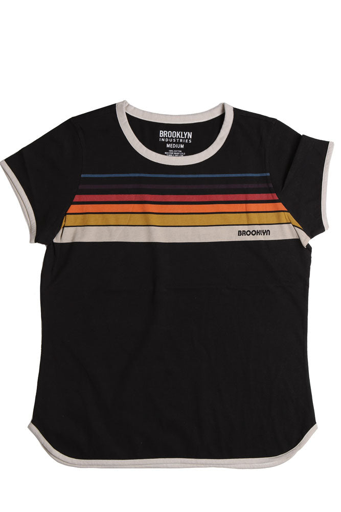 Flat lay, black t-shirt with white rim detail, and retro rainbow detail across the chest, with brooklyn writtin on the bottom color.