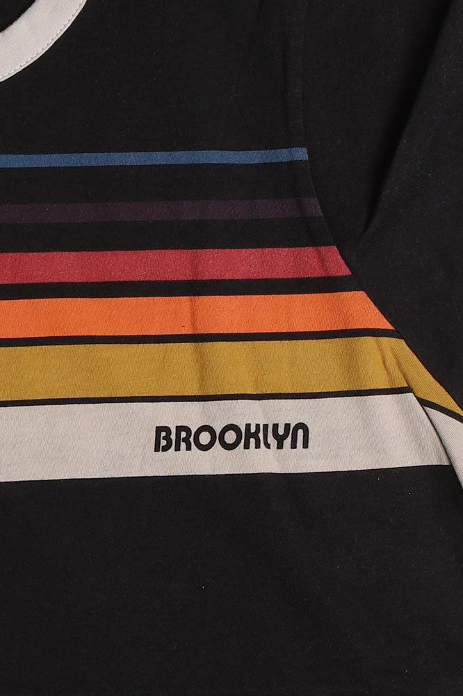 detail Flat lay, black t-shirt with white rim detail, and retro rainbow detail across the chest, with brooklyn writtin on the bottom color.