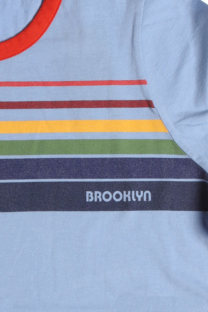 detail of Flat lay, blue t-shirt with white rim detail, and retro rainbow detail across the chest, with brooklyn writtin on the bottom color.