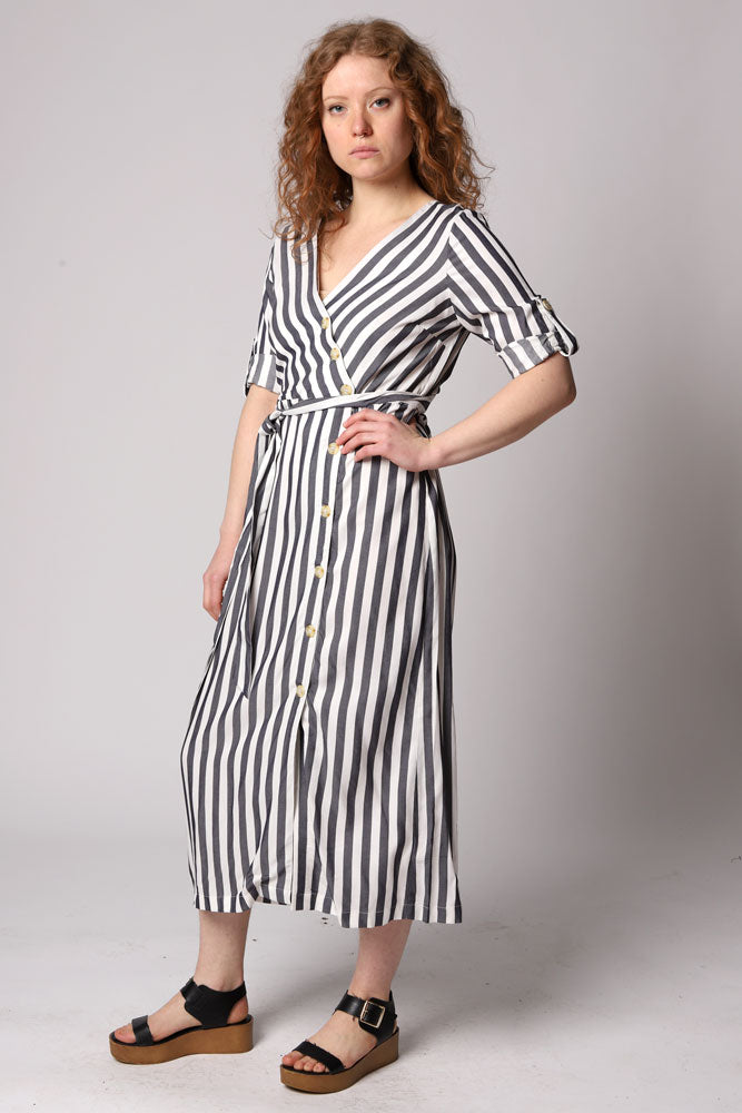 A striped rayon midi dress with an asymmetric crossover button front detail, waist tie, and rolled cuff sleeves. Button and front tie closure.