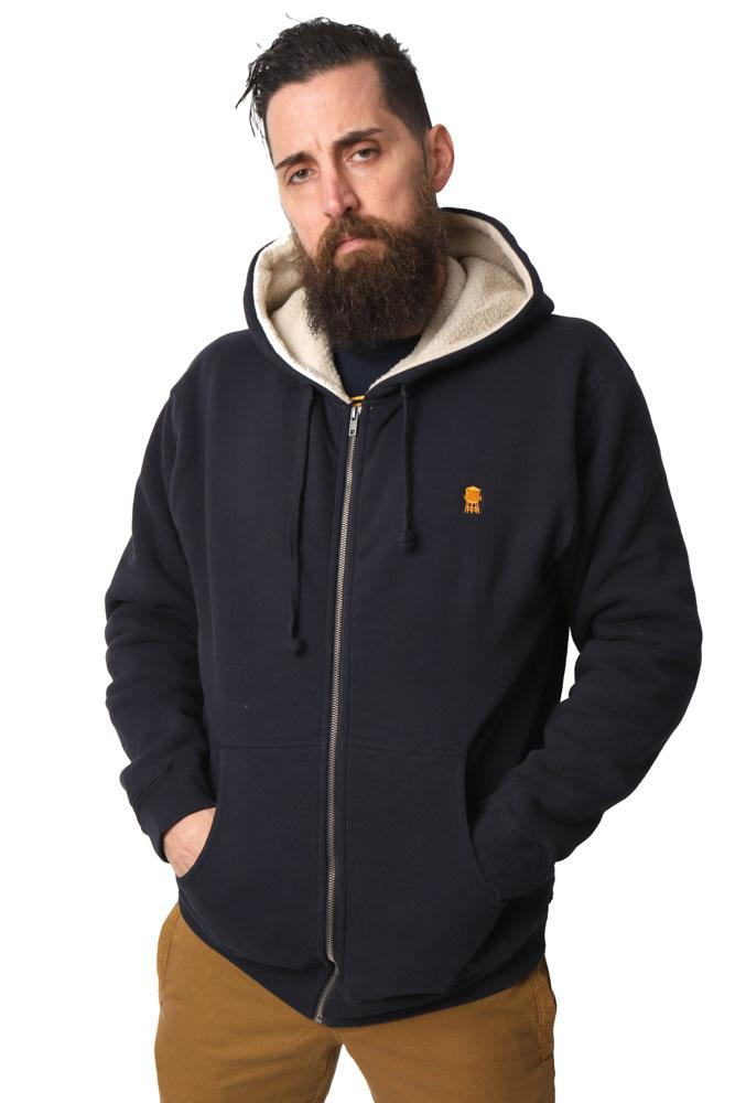 man looks at camera wearing blue hooded sherpa lined sweatshirt with orange water tower embroiderd on the left chest.