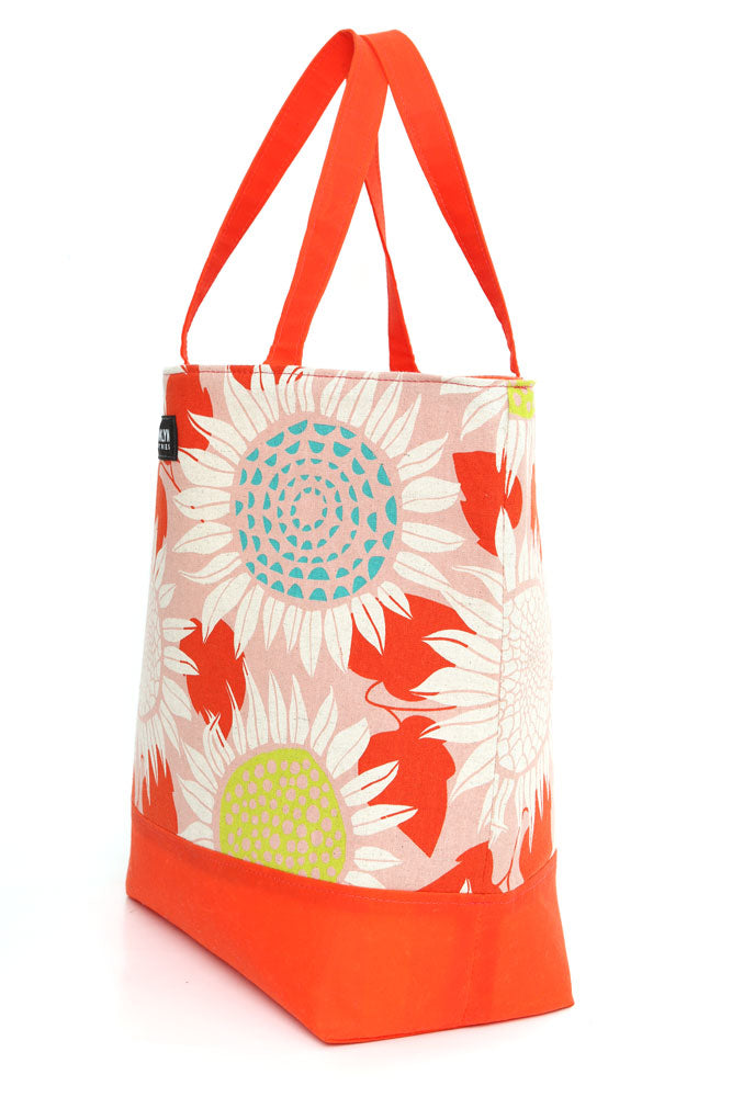 SIDE VIEW CANVAS TOTE BAG WITH SUNFLOWER GRAPHIC DESIGN TOP PANEL AND WAXED CANVAS IN ORANGE BOTTOM AND STRAPS