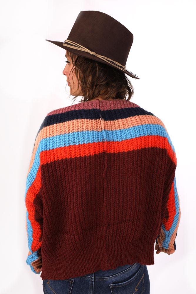 back view of women in flat brim brown hat and maroon bodied chunky sweater with red, blue orange and light pink stripes