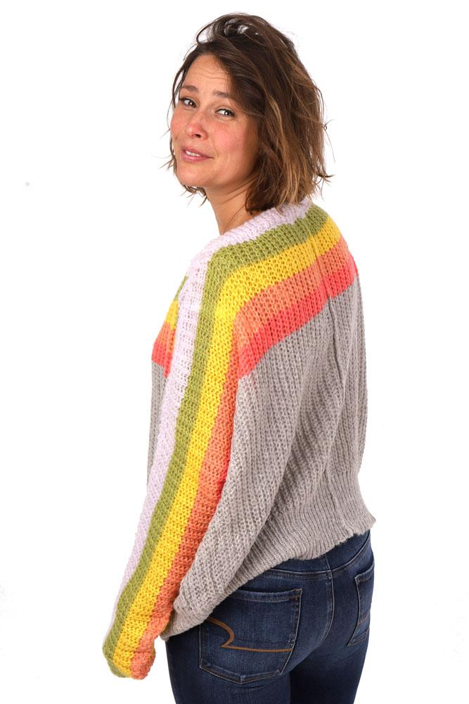 back view , women looks over her shoulder in chunky off the shoulder striped sweater in charcoal, orange,yellow green and light pink