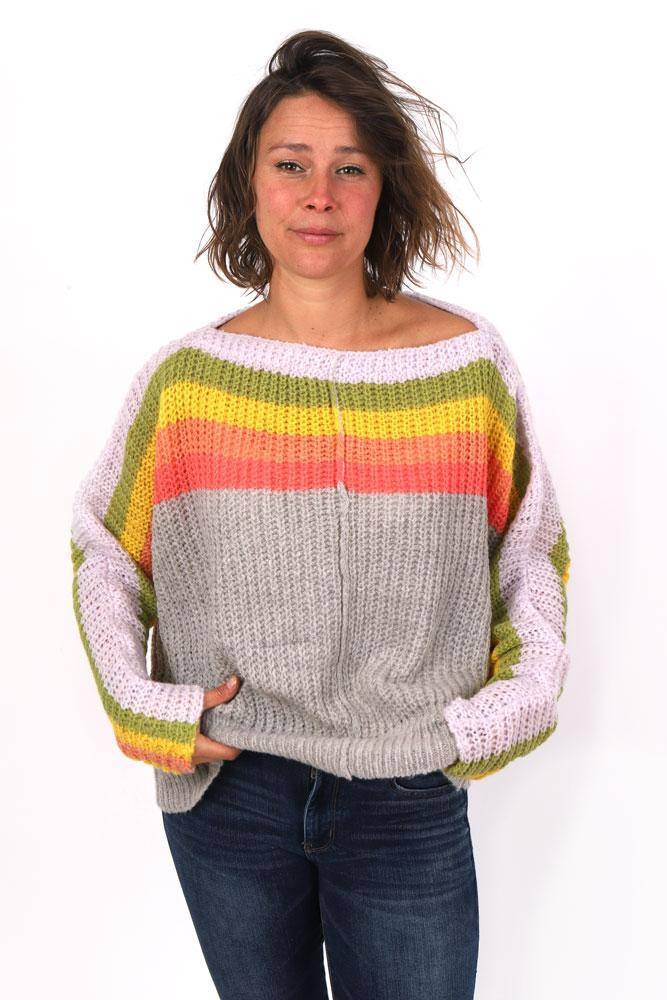 women smiles with messy hair, hands in jeans pocket, wearing chunky off the shoulder striped sweater in charcoal, orange,yellow green and light pink