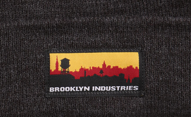 DETAIL OF SKYLINE PATCH ON BEANIE IN GREY
