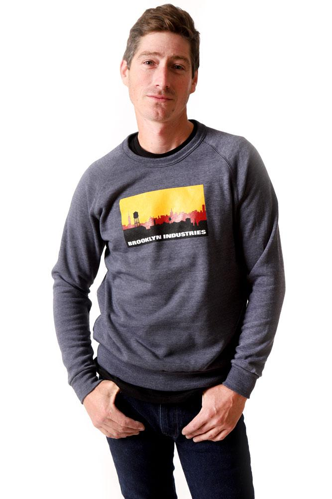 MALE MODEL STANDS CROOKED WITH HANDS IN POCKETS WEARING SKYLINE SWEATSHIRT