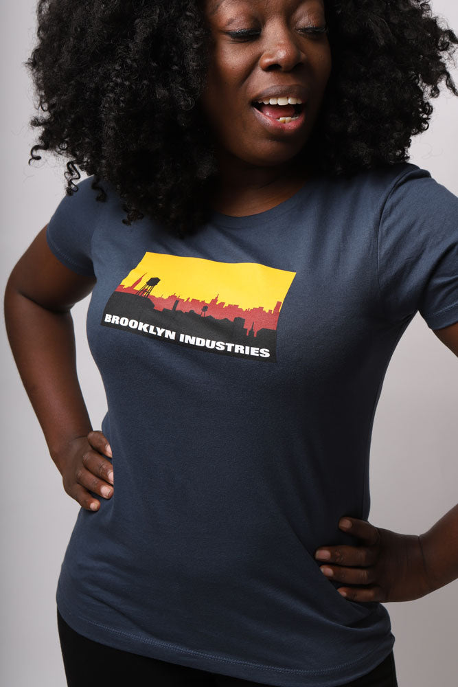 women smiles with hands on hip in skyline logo shirt in indigo