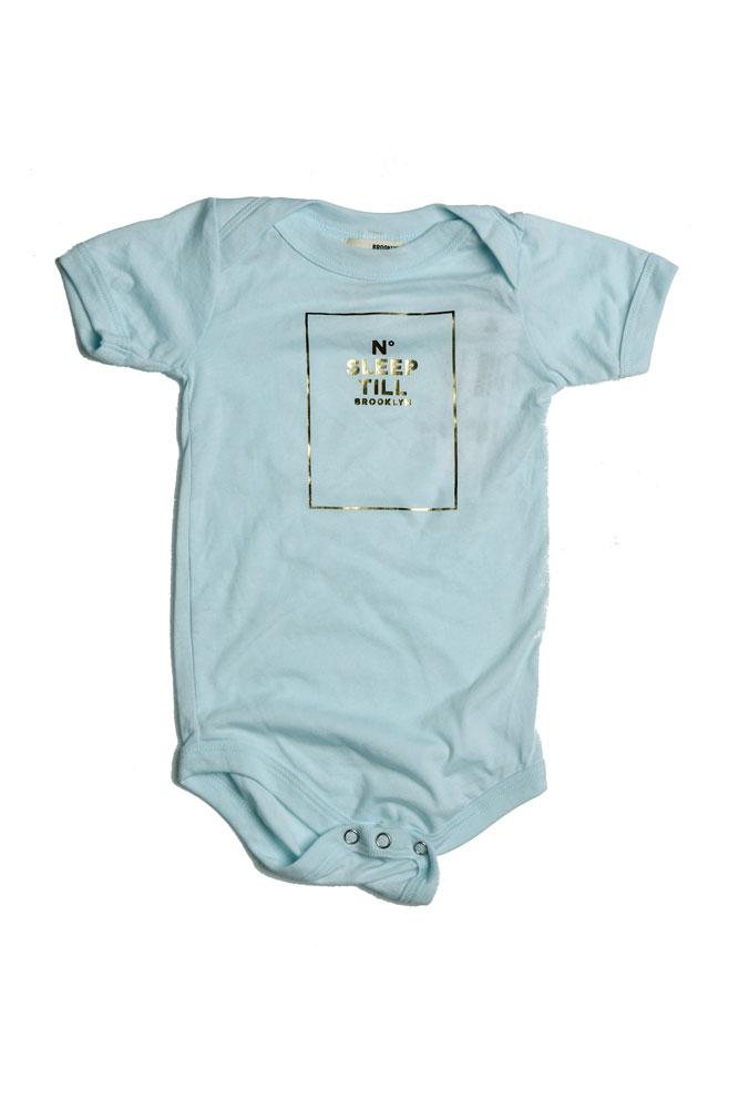 flat lay ice blue baby onesie with gold foil no sleep til brooklyn